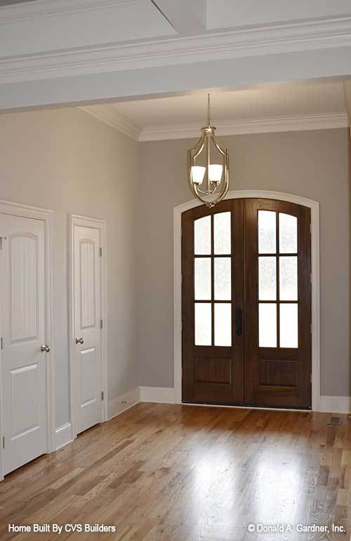Foyer with an arched front door, brass pendant light, and a natural hardwood flooring.