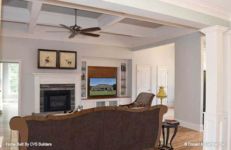 The living room offers a glass-enclosed fireplace, cozy brown seats, and a chrome ceiling fan that hangs from the coffered ceiling.