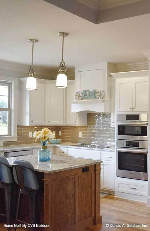 A pair of glass pendant lights hanging above the center island illuminates the kitchen.