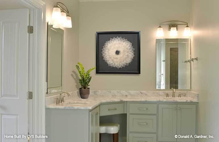 The primary bathroom features a dual sink vanity complemented with frameless mirrors and a stylish wooden stool.