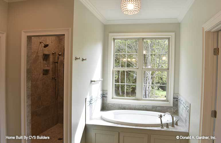 The opposite side shows the walk-in shower and a deep soaking tub fixed under the white framed window.