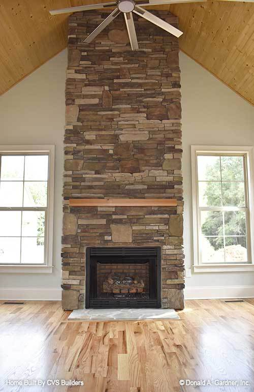Spacious sitting room with a stone fireplace and a ceiling fan mounted on the cathedral ceiling.