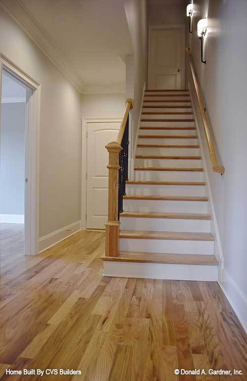 A traditional staircase with white risers and wooden treads matching with the light hardwood flooring.