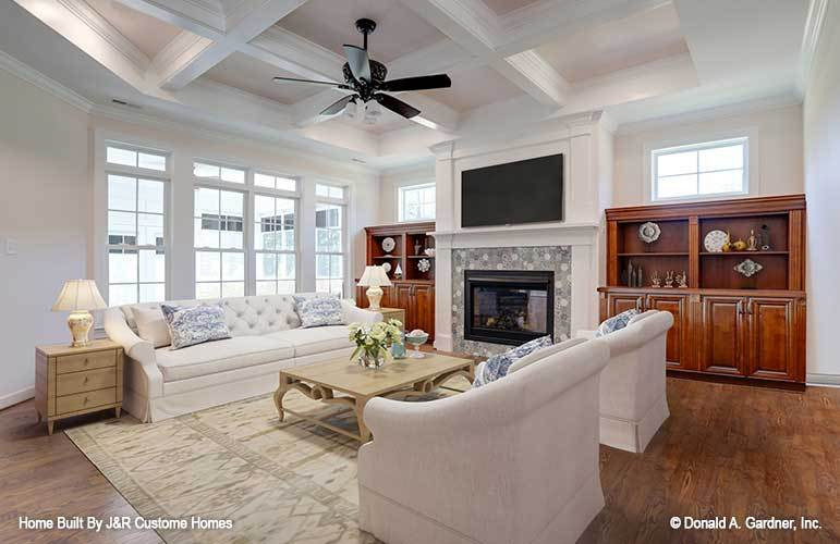 Living room with beige skirted seats, wooden coffee table, and a fireplace with a TV on top.
