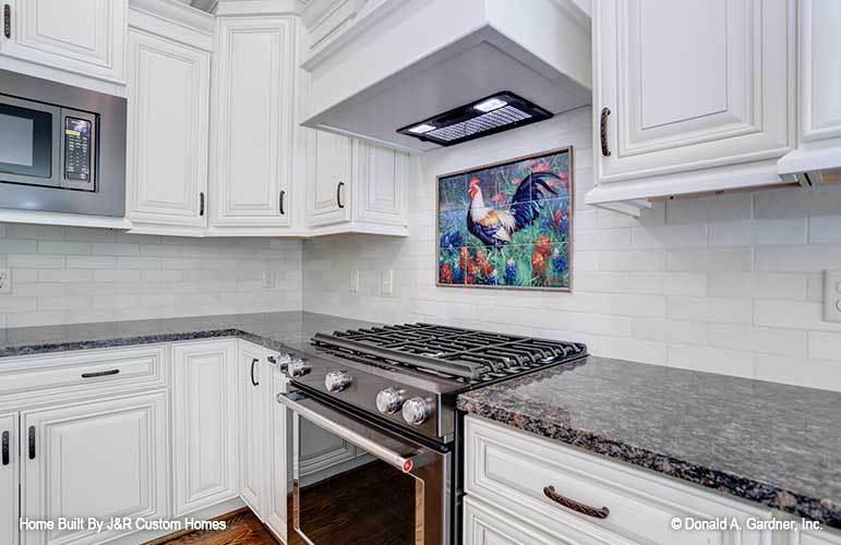 A decorative rooster tile backsplash stands out against the white cabinets and subway tile backsplash.