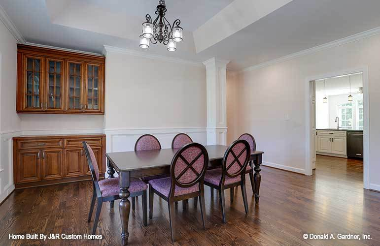 The dining room offers a built-in cabinet, cushioned round back chairs, and a dark wood dining table well-lit by an ornate chandelier.