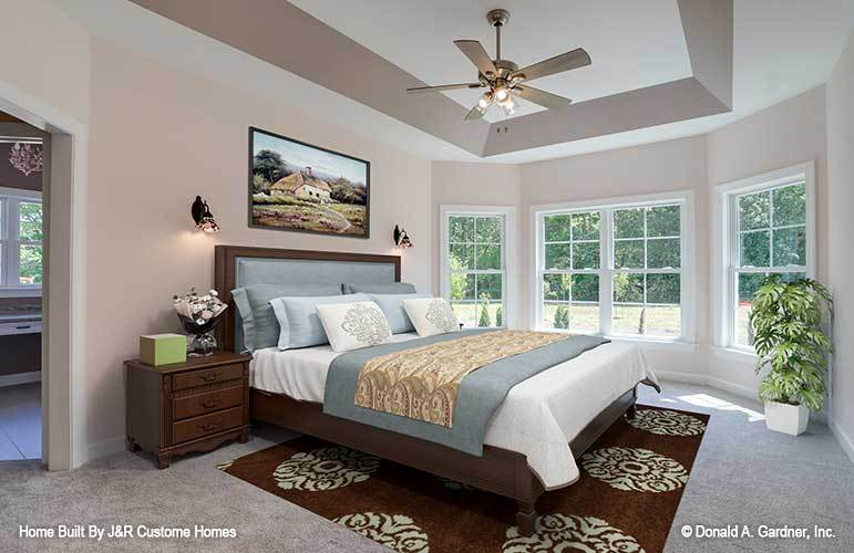 Primary bedroom with wooden furnishings, tray ceiling, and a bay window that invites natural light in.