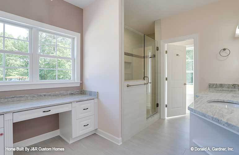 The primary bathroom has a walk-in shower and white vanities topped with granite countertops.