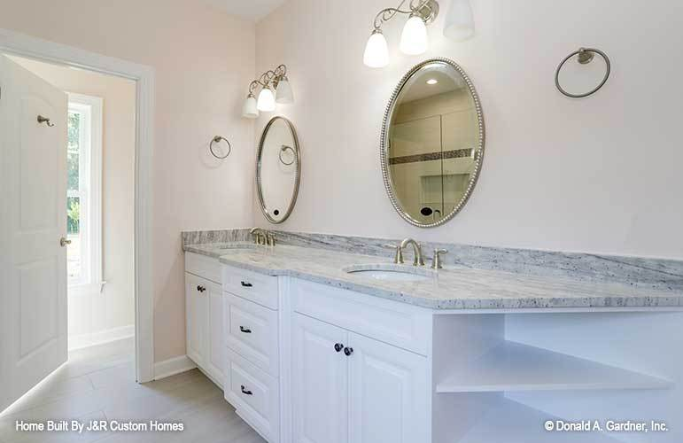 Glass sconces and round mirrors complement the dual sink vanity.