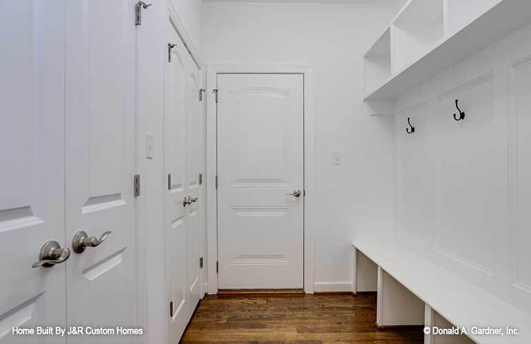 The mudroom is filled with two sets of french doors and built-in storage with white shelves and wrought iron hooks.
