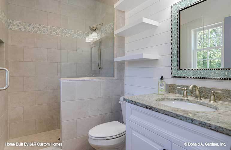 This bathroom has a walk-in shower, a toilet, floating shelves, and a sink vanity paired with a stylish mirror.