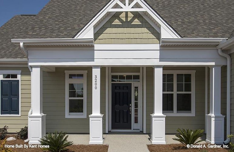 Covered front porch with a dark wood entry door, tapered columns, and a gable roofline adorned with white decorative trims.