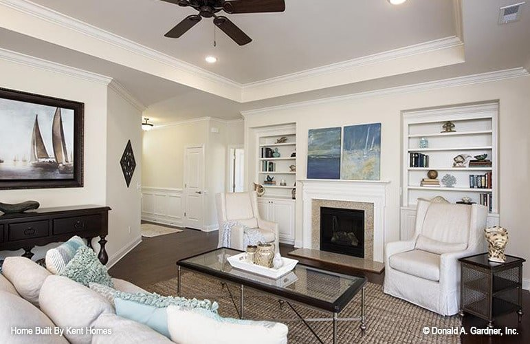 The living room has beige skirted seats, glass top coffee table, and a glass-enclosed fireplace flanked with inset built-ins.
