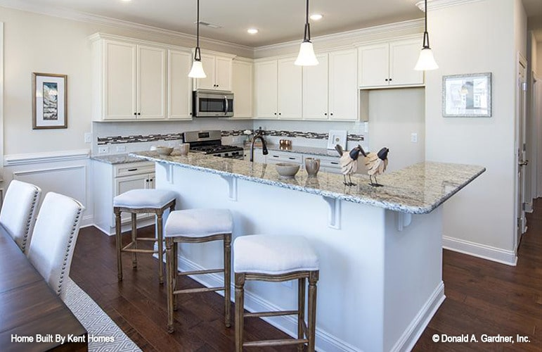 Kitchen with white cabinets, granite countertops, and a breakfast island complemented with glass pendants and cushioned stools.