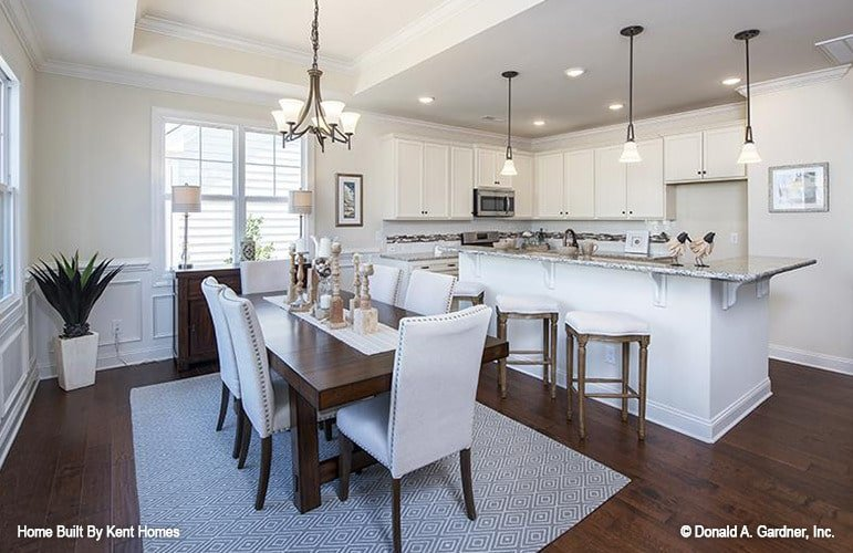 The dining area offers a patterned area rug, gray upholstered chairs, and a dark wood coffee table that matches the hardwood flooring.