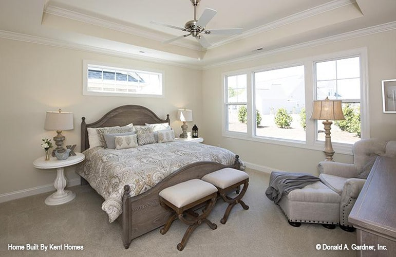 Primary bedroom with white framed windows, beige carpet flooring, and a tray ceiling mounted with a brass fan.