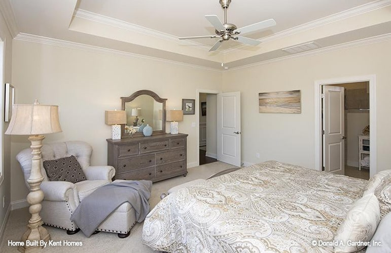 The primary bedroom is furnished with a wooden vanity, a cozy bed, and a tufted lounge chair lit by a light wood floor lamp.
