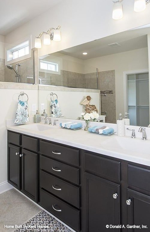 Dual sink vanity with black cabinets, quartz countertop, and a frameless rectangular mirror.