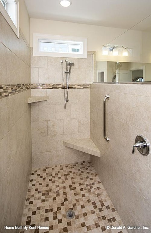 Walk-in shower with beige marble tiled walls, corner shelves, chrome fixtures, and mosaic tiled floor.