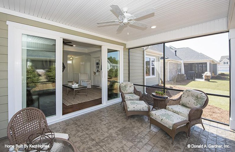 The screened porch is filled with wicker cushioned seats, round tables, and a white fan hanging from the shiplap ceiling.