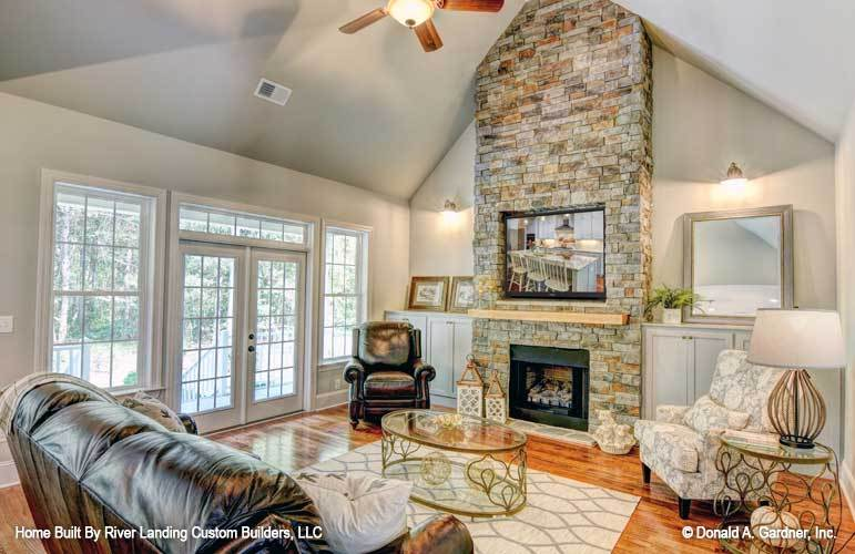 The living room offers black leather and floral seats, glass top tables, and a stone fireplace flanked with white cabinets.