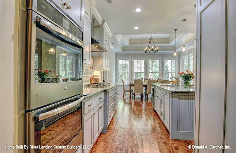 Galley kitchen overlooking the dining area that's crowned with a step ceiling.