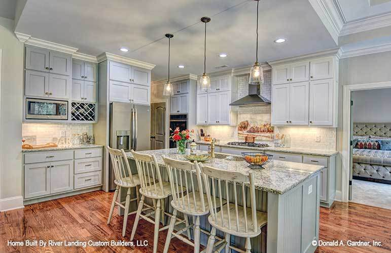 The kitchen is equipped with light gray cabinetry, stainless steel appliances, granite countertops, and a beadboard island.