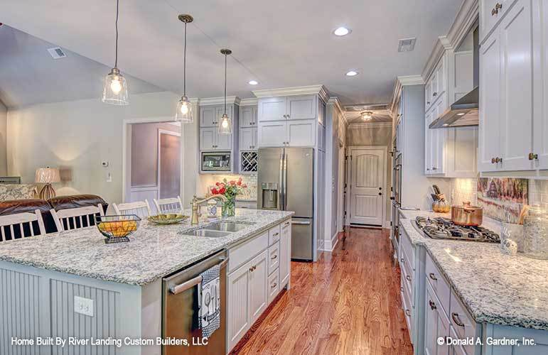 Recessed ceiling lights along with glass pendants that hang over the center island illuminate the kitchen.
