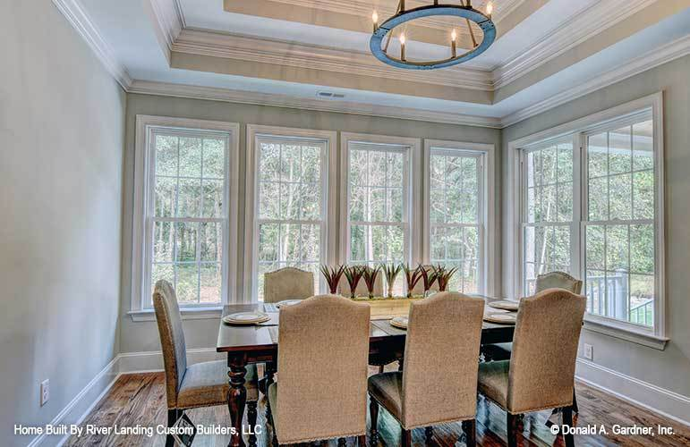 The dining area offers beige upholstered chairs, dark wood dining table, round chandelier, and plenty of white-framed windows.