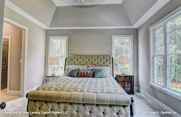 Primary bedroom with a coved ceiling, gray carpet flooring, and a beige tufted bed nestled in between the ornate and wooden nightstands.