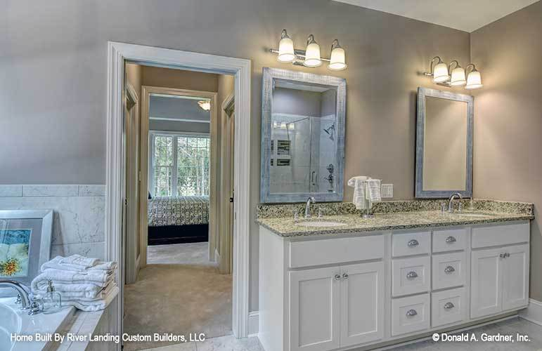 White vanity on the side showcases a granite countertop, two undermount sinks, and a pair of wooden framed mirrors.