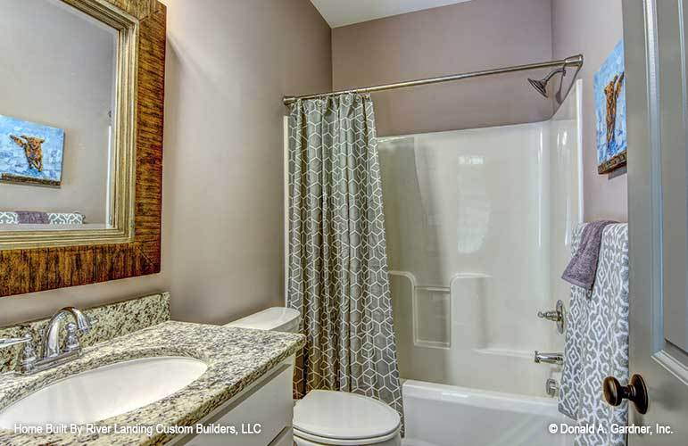 The other bathroom is equipped with a sink vanity, a toilet, and a tub and shower combo enclosed in a patterned curtain.