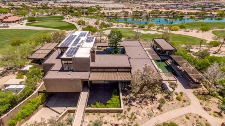 This is an aerial view of the contemporary-style home with an earthy brown tone to its exteriors that have straight lines and angles complemented by a desert landscape with walkways and driveways. Image courtesy of Toptenrealestatedeals.com.