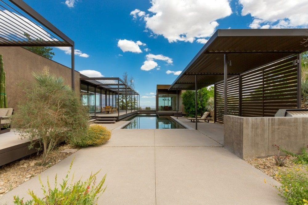 This is a look at the back of the house with a large pool, concrete walkways and steel structures that have an earthy tone. Image courtesy of Toptenrealestatedeals.com.