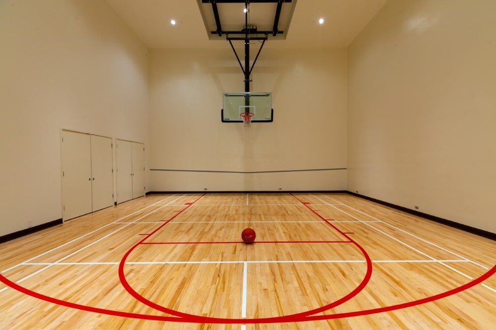This is the subterranean basketball half-court with a tall beige ceiling that has bright recessed lights. Image courtesy of Toptenrealestatedeals.com.