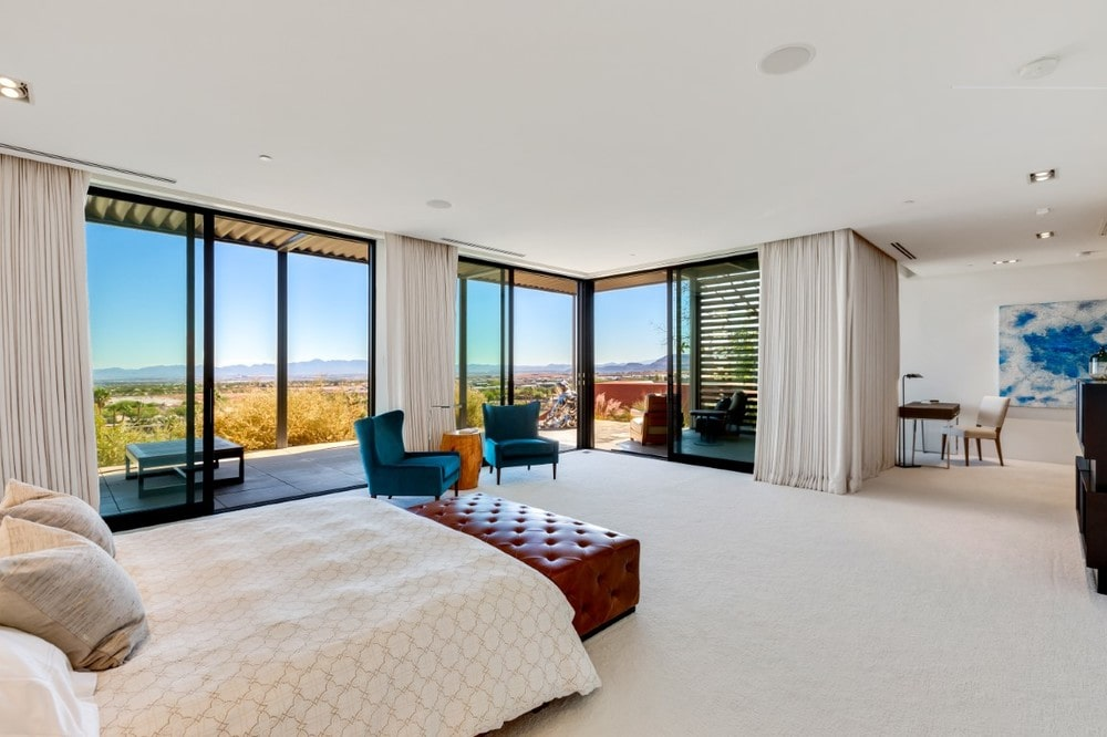 This is a spacious bedroom with a bed that blends with the beige walls, ceiling and floor. These are then complemented by the red leather cushioned bench at the foot of the bed and the pair of green cushioned chairs by the glass walls. Image courtesy of Toptenrealestatedeals.com.