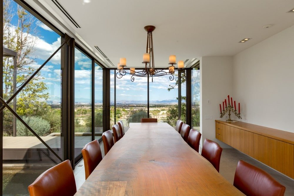 This is a close look at the dining room with a large rectangular wooden dining table surrounded by red leather chairs, topped with a chandelier and brightened by the glass walls. Image courtesy of Toptenrealestatedeals.com.