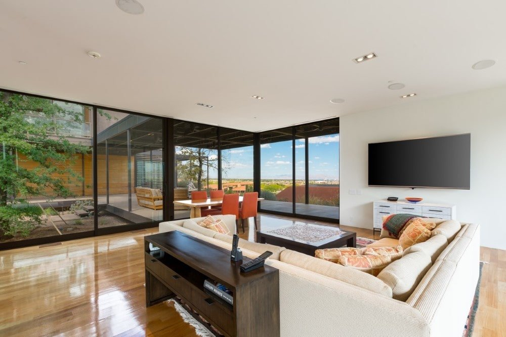 This is the bright and airy family room with a large L-shaped sectional sofa to match the beige walls and ceiling. These are then contrasted by the hardwood flooring and the black frames of the glass walls. Image courtesy of Toptenrealestatedeals.com.
