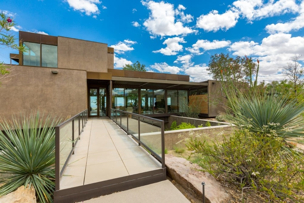 This is a look at the front of the house featuring the main entrance with concrete walkway bordered with glass to match the glass walls and glass doors of the house that stands out against the earthy tone of the exteriors. Image courtesy of Toptenrealestatedeals.com.