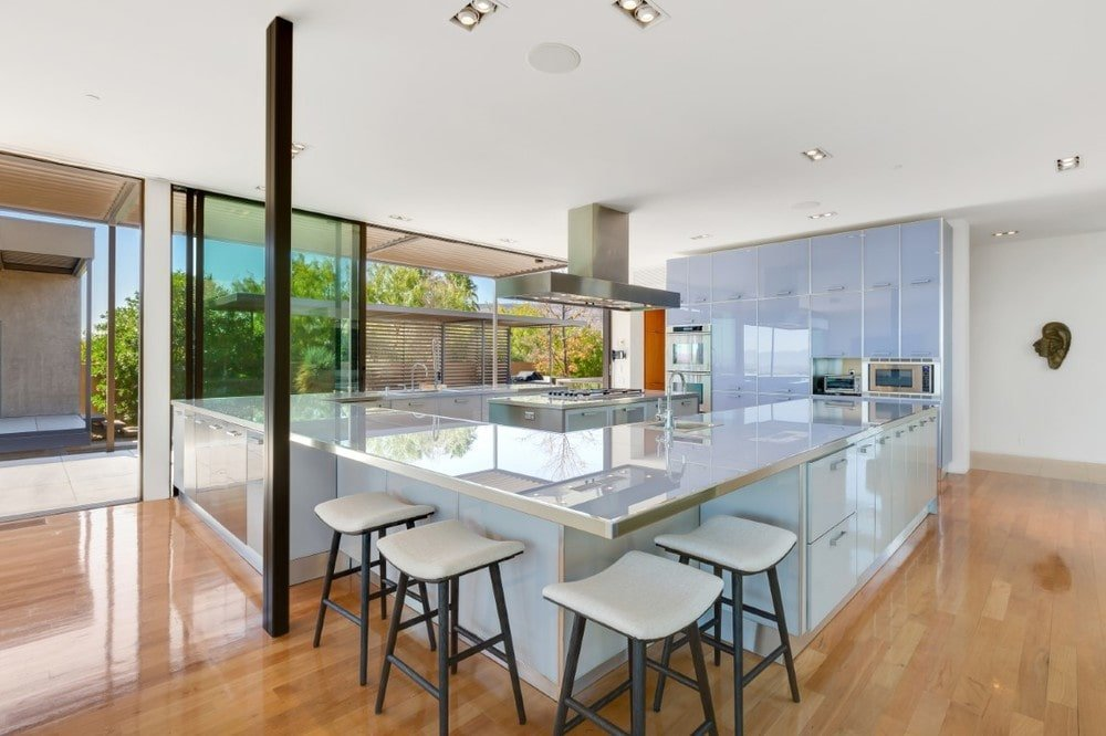 This is the large kitchen of the house with a large U-shaped peninsula adorned with frosted glass cabinetry and matching countertop that has a breakfast bar at the corner. Image courtesy of Toptenrealestatedeals.com.