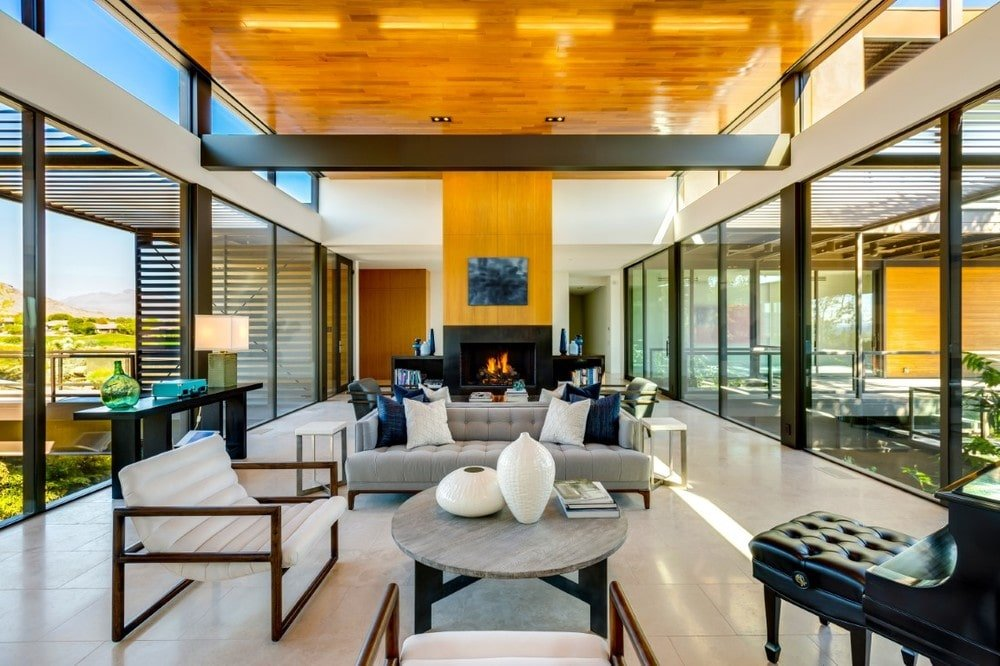 This is a spacious living room with a tall wooden ceiling complemented by the exposed metal beam and the glass walls on two sides that bring in an abundance of natural lighting. Image courtesy of Toptenrealestatedeals.com.