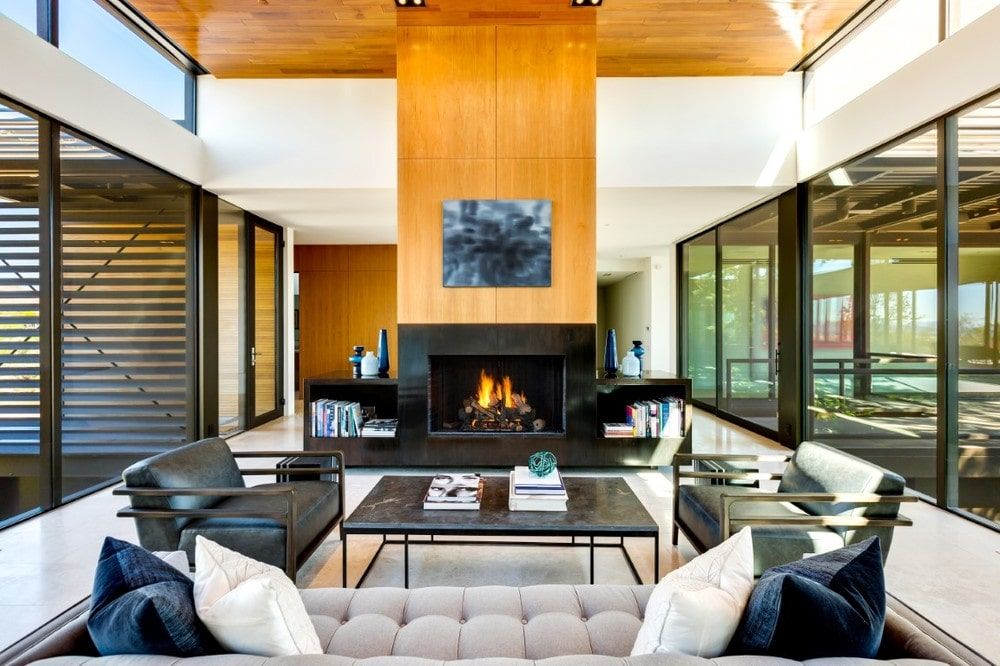 This closer look at the spacious and bright living room showcases the tall wood-paneled pillar that houses the fireplace across from the beige sofa that is paired with a couple of black leather armchairs. Image courtesy of Toptenrealestatedeals.com.