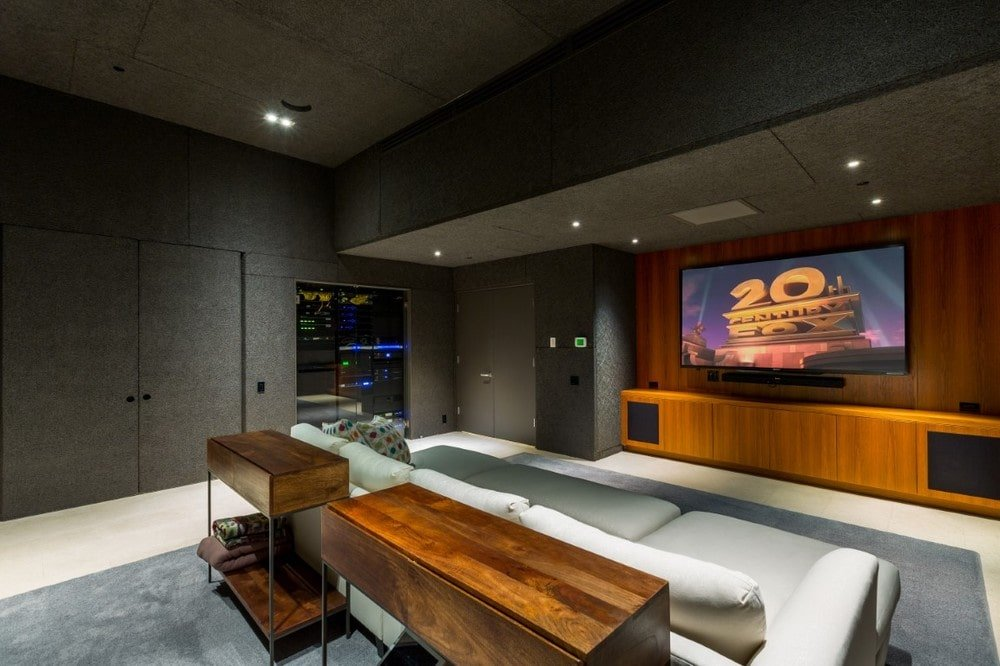 The home theater room has a large wall-mounted screen at the far wall across from the large comfortable couch that stands out against the dark gray walls and ceiling. Image courtesy of Toptenrealestatedeals.com.