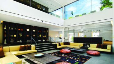 This is the spacious living room with a tall ceiling, glass walls and colorful furniture to contrast the black elements. Image courtesy of Toptenrealestatedeals.com.