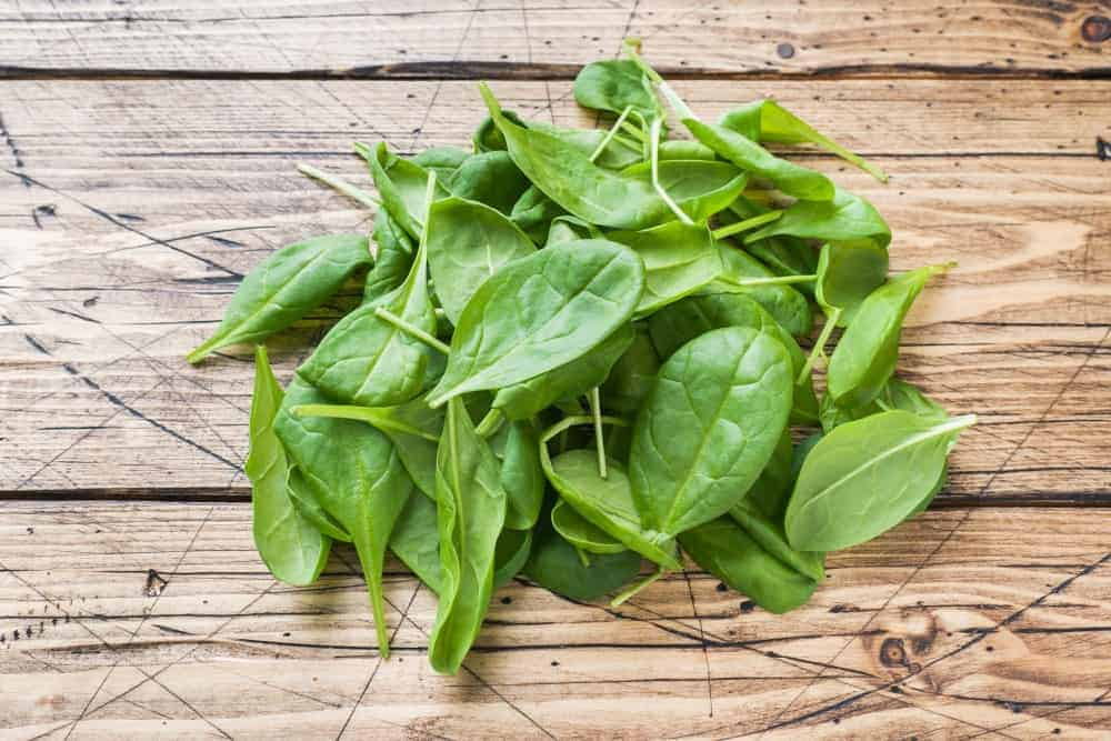 Spinach Leaves on a rustic wood plank table.