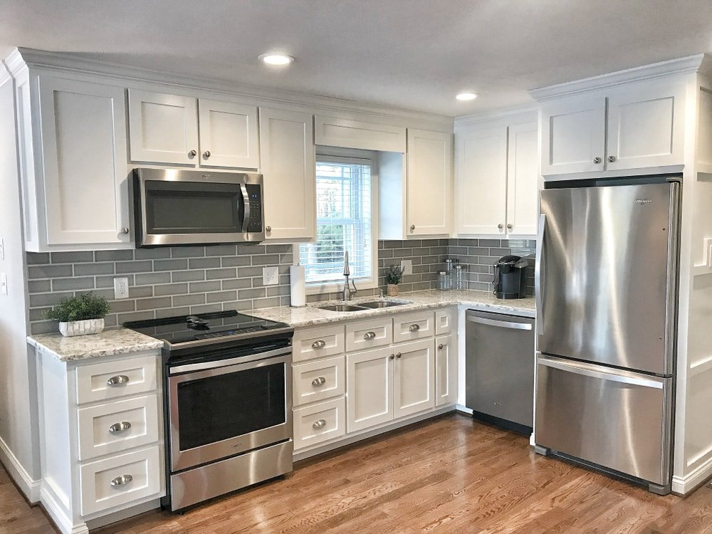 Kitchen with white cabinets, gray tile backsplash, and stainless steel appliances.