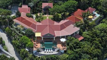 This is an aerial view of the side of the house facing the cliff. You can see here the U-shaped house with a terracotta tone to its roof that contrasts the surrounding tall trees. Image courtesy of Toptenrealestatedeals.com.