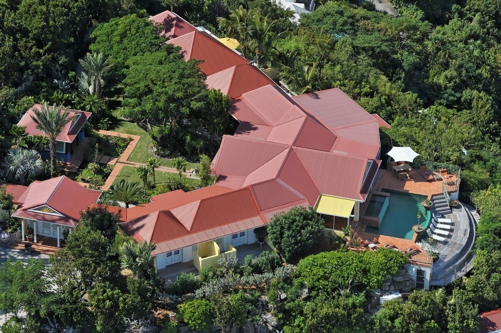This is an aerial view of the house that features the opposite side of the property that has a green courtyard, a covered patio and walkways that lead to the various areas of the house. Image courtesy of Toptenrealestatedeals.com.