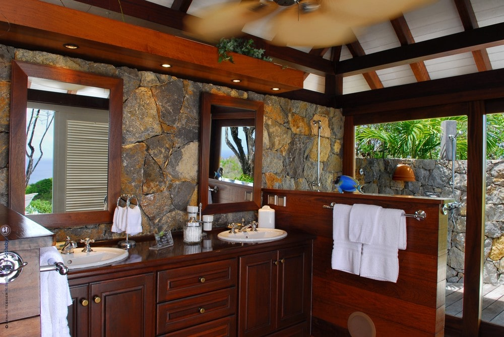 This is a look at the bathroom with dark wooden cabinetry and window frames that stand out against the mosaic stone walls. Image courtesy of Toptenrealestatedeals.com.