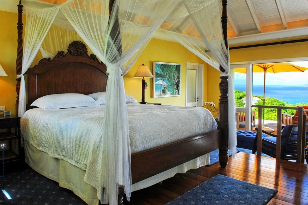 This bedroom has a large wooden four-poster bed with white curtains on the corners. These make it stand outa gainst the beige walls that are illuminated by the natural light coming in from the terrace. Image courtesy of Toptenrealestatedeals.com.